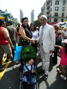 New York State Assemblymember Guillermo Linares (right) greets community residents during the Juan Pablo Duarte Foundation's Carnaval celebration.
