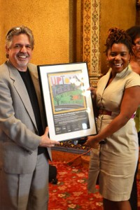 Publisher Luis Miranda presents award-winning playwright Katori Hall with her framed award in light of her contributions to the arts in northern Manhattan.
