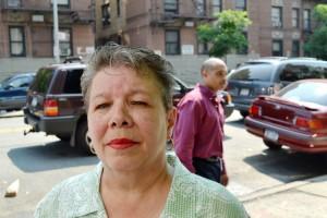 """Ramona de los Santos, residente de un edificio por más de 30 años antes del desplazamiento, sonríe. """"Estoy lista para regresar a casa ya; prácticamente tengo los patines puestos""""."""