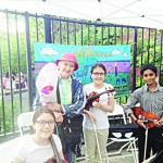 Jeanlee Poggi (with hat) of the West 181st Street Beautification Project stands with youth orchestra musicians.