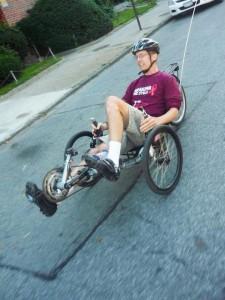 Payne montando su bicicleta especial truqueada de tres ruedas.