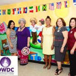 The mural artists stand with DWDC Executive Director Rosita Romero (center, in yellow).