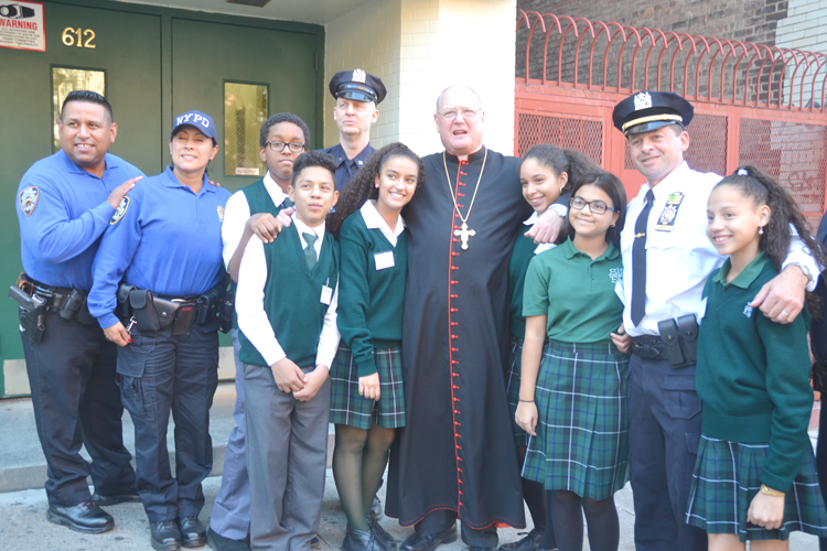 Cardinal Timothy Dolan, with students and NYPD members, visited St. Elizabeth School.