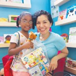 Anaya-Cerda with a young reader at the shop's one-year anniversary celebration.