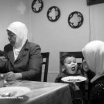 Eman feeds her son, Hassan, a traditional Syrian dish of Maqlooba during dinner in their apartment.
