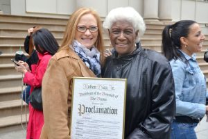 Alexandra Smith (right), Program Director for Denim Day NYC, stands with proclamation and Greene.