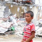 A young boy surveys the damage in his village.