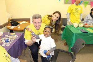 Ryan Serhant (center) of the Bravo television series Million Dollar Listing New York hung out with a young patient at EHACE.