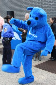 Blu (center), the WellCare Bear Mascot in New York, busts a move.