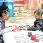 Elijah, 7, takes on his mother Simone in checkers.