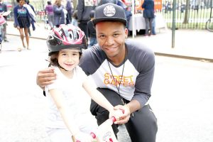 Elena, 4, goes for a ride with her bike instructor Rodney.
