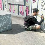 A WHAC member volunteers on the mural.