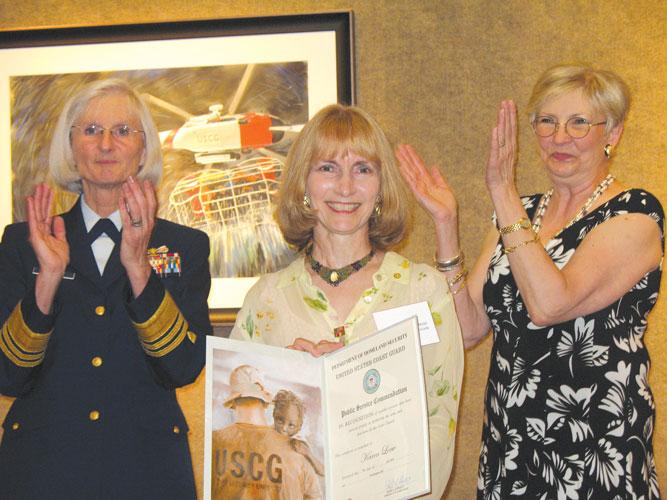 Artist Karen Loew (center) receives the United States Coast Guard (USCG) Public Service Award.