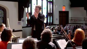 Chris Whittaker (standing) is a conductor and composer.