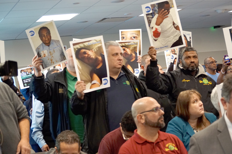 Signs were held up during the hearing.
