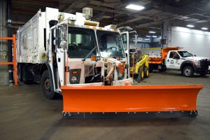 Garbage collection trucks are fitted with front plows.