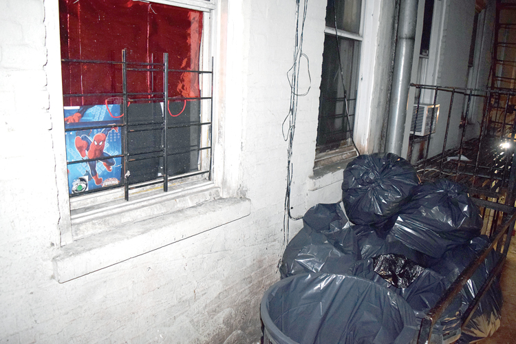 The outdoor trash bins are placed right next to apartment windows.