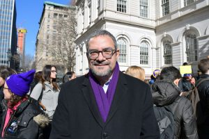32BJ President Hector Figueroa stands with workers.