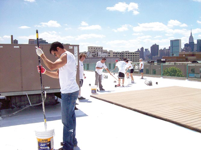 Workers apply reflective coating to building rooftops.