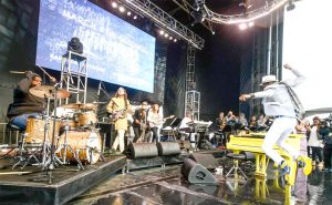 Jon Batiste (leaping on the left) performed on stage.