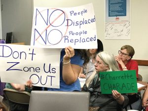 Residents hold up signs of protest at a community board meeting.