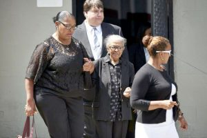 Familia's mother Adriana Valoy (center) is comforted by family members.