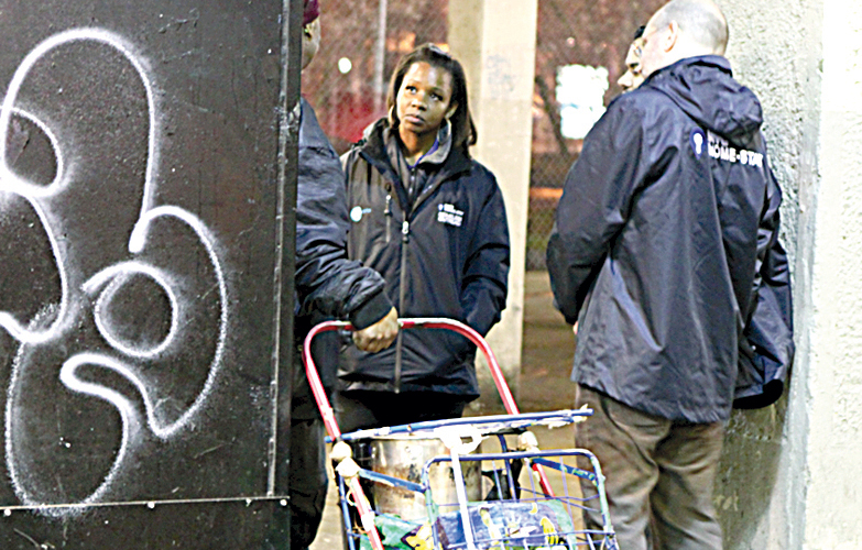 The city's HOME-STAT members engage homeless individuals in the street.
