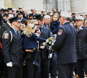 Davidson's daughter, held by mother Eileen, reaches for his father's helmet. Photo: FDNY