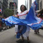 A folkloric dancer makes her way down Sixth Avenue.
