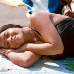 Una mujer joven se empapa en los rayos.