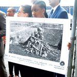 Un estudiante sostiene una imagen de restos de esclavos colocados en una pila.