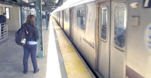Woman next to train pulling into subway platform